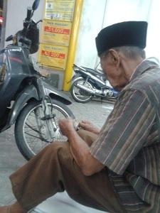 bapak tua tukang parkir menghitung uang